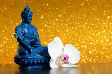 Blue Buddha statue and a orchid flower on a bright gold shiny glitter background with bokeh