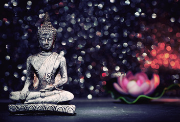 Buddha statue and a lotus flower on a bright shiny background with bokeh. Photo in vintage style