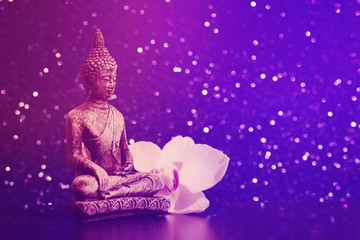 Buddha statue and a orchid flower on a bright shiny background with bokeh. Photo in vintage style