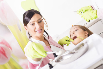 Girl having teeth examination at dental clinic.