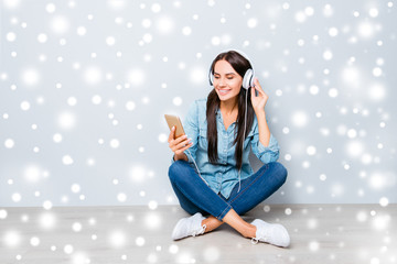 Young happy girl sitting on floor and listening music on winter