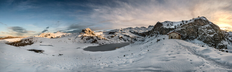 Covadonga lakes beautiful snowy winter landscape scene at rural location of Asturias, Spain, Europe, surrounded by mountains. Refuge house in Snow relax leisure destination for holidays or vacations.