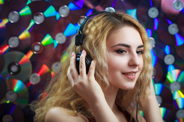 Concept: hipster lifestyle, relaxation. Beautiful young woman in headphones have fun and listen music with colorful CD's on background.