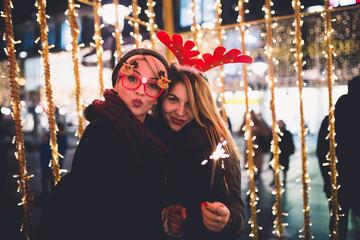 Beautiful young women enjoying Christmas or New Year night on a city street.