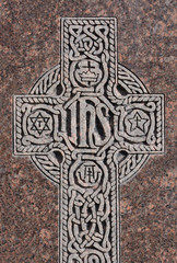 "Close up if engraved Celtic Cross with Christogram ""IHS"" on gravestone"