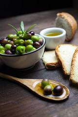 Olives And Bread With Spoon On Table