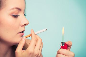 Girl using lighter to light cigarette.