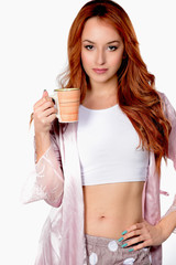 Portrait of lovely redheaded woman siting on big pillow holding drinking cup of coffee, tea, on white background