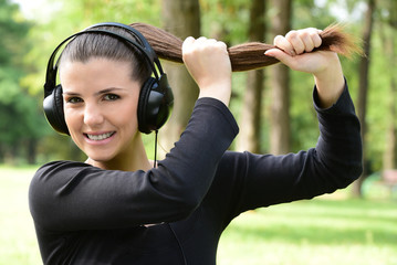 Young happy surprised woman with headphones listening to music outdoors in the park