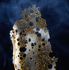 Detail of marijuana oil concentrate aka shatter isolated on blac