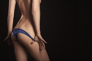 undressing panties from tan slim female body on black background with copyspace