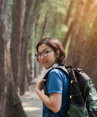 Asian glasses woman hiker with backpack and headphone smiling on nature background.