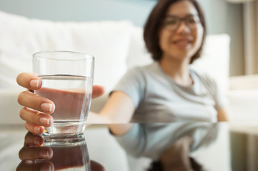 Asian glasses woman holding glass of water for drink. Woman smiling. Happiness, fresh.