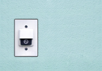 Doorbell or buzzer on mounted on green wall