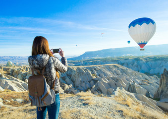 Female tourist taking photos of hot air balloon in Cappadocia