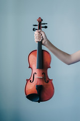 hand holding violin against a blue wall