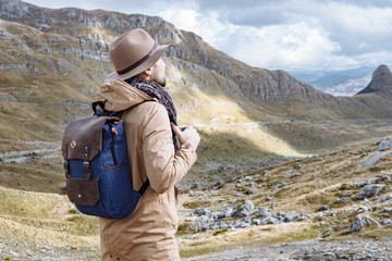 Young man in Hat with backpack starting an adventure in the moun