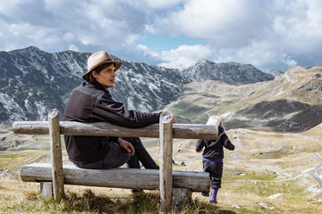 Father and little daughter travel in autumn mountains, Montenegr