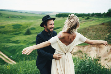 Joyful bride and groom in the lap of the nature