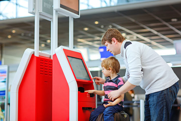Father and little kid boy at the airport, traveling together