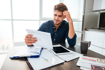 Confused man holding head with hand and looking at documents