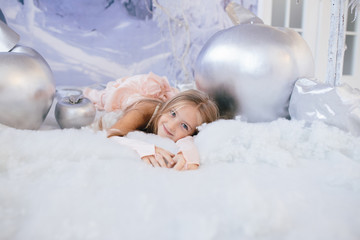 cute little girl in an elegant pink dress in winter decoration