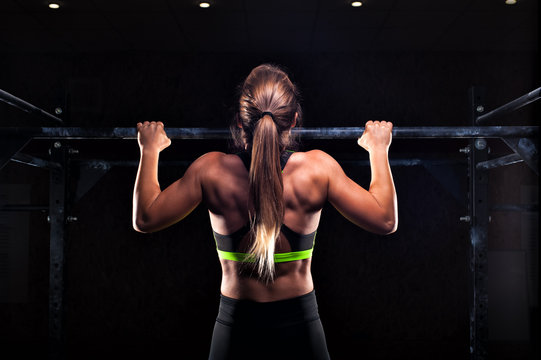 Strong girl in sportswear doing pull up exercise