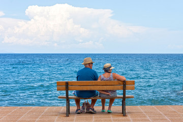 A copy of seniors sitting on a bench at sea shore
