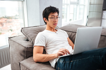 Side view of asian man with laptop on sofa