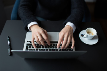 Woman's hands typing on notebook