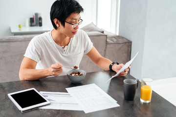 Asian man working and eating