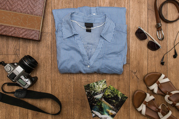 Travel and tourism concept - set of stuff with shirt, headphones, film camera, belt, glasses, photo and shoes on wooden table background.