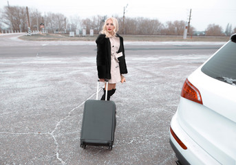 Business woman with suitcase near the car. Standing on the background road