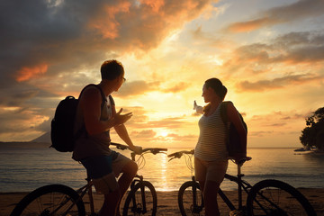 Happy couple tourists with bicycles watching sunset. Silhouette people