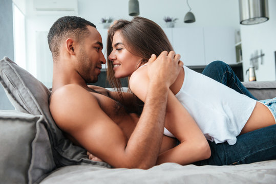 Tender young couple lying and hugging on couch