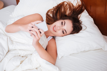 Woman lying in bed and typing message on mobile phone