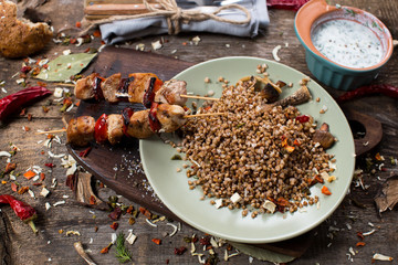 Buckwheat with sauce and chicken kebabs on skewers on a plate