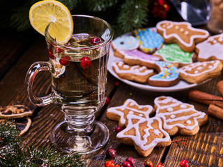 Christmas cookies on plate under fir branches. Christmas still life with mug decoration lemon slice hot drink on wooden table.
