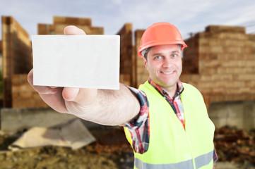 Successful male builder holding visit card in closeup