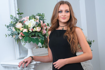 Beautiful woman in a black dress near mirror and the flowers in