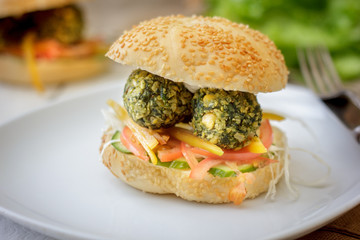 Shot of falafel burger whith the fresh vegetables and falafel balls inside it.