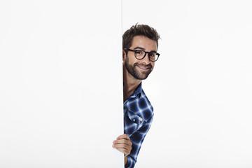 Smiling guy in glasses in white studio