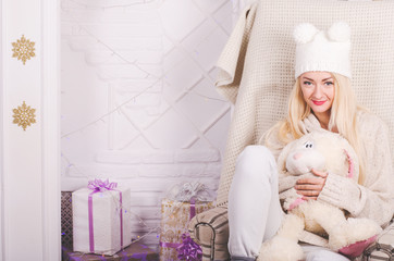 Girl in a funny hat hugging a cute bunny in a cozy chair christmas setting, light colors