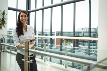 Smiling businesswoman holding mobile phone in office corridor