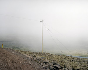 an electricity pole in the mountains in iceland in the mist