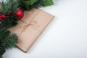 Kraft gift box with christmas balls and tag on a white background