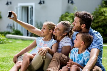 Happy mother taking selfie with family in yard