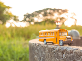 yellow school bus plastic and metal toy model on the country roa