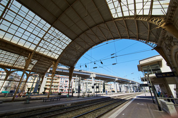 Aluminium Prints France, Nice, 15 august 2016: Panorama of the railway station in the center, sunny day, blue sky, a lot of tourists, Rails under glass a roof, in front of shaped visor, sncf, gare