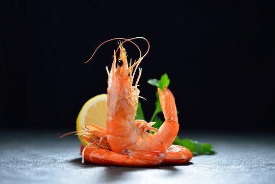 Cooked shrimps,prawns with seasonings on black stone background